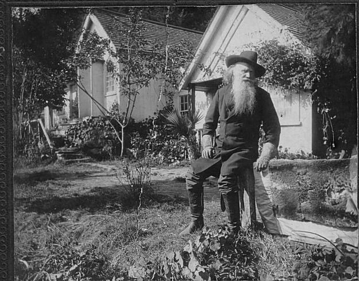 Oakland poet Joaquin Miller posing on his land in front of the cottages he named ?'the Abby.?