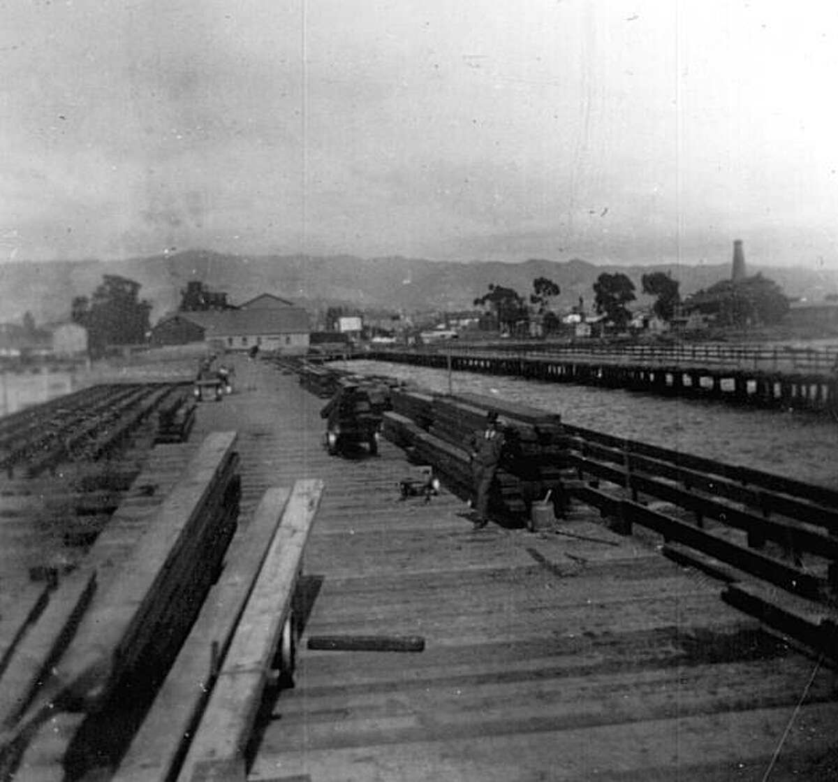 About ten minutes after the quake, what was described as a wall of water five feet tall slammed into the West Berkeley Lumber Company?•s wharf, destroying more than a hundred feet of the wharf and washing away an estimated fifty thousand feet of lumber. An employee, B. J. Rose, was securing a stack of lumber to a piling when the wave hit. He was thrown into the bay but was able to climb out to safety. The tall chimney stack on the far right was part of the 1876 O?•Neil Glass Factory. Richard Schwartz presented the facts of this event, lost to history and science, to the USGS. Specialists at the USGS ran a computer simulation and thought it likely the incident was caused by an underwater collapse of part of Yerba Buena Island, causing the localized ?'wall of water.?