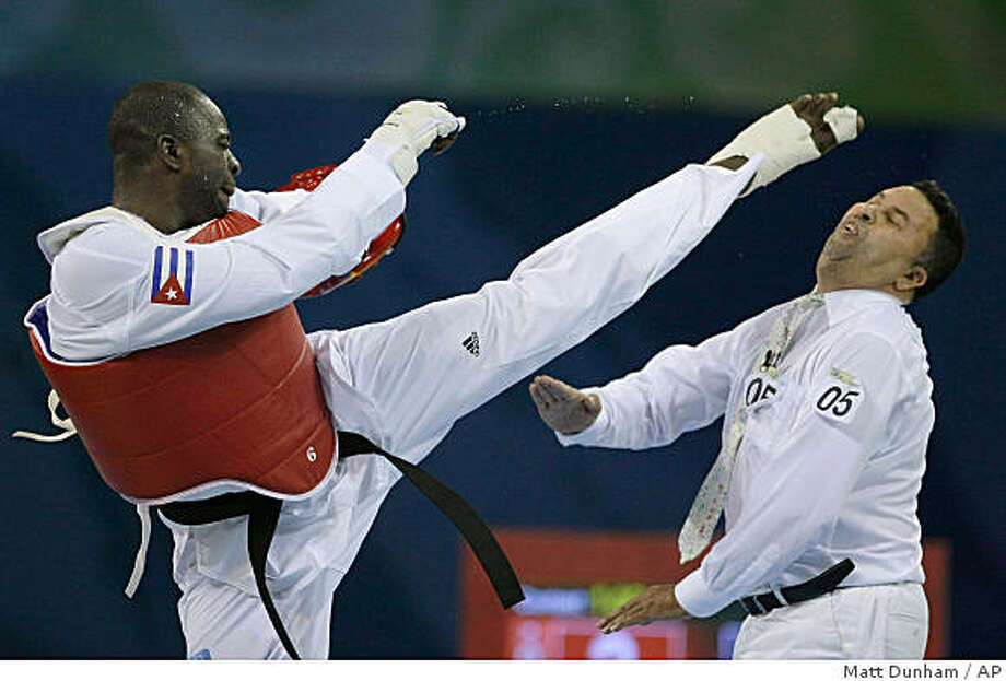 Cuba's Angel Valodia Matos, left, kicks match referee Sweden's Chakir Chelbat in the face during a bronze medal match against Kazakhstan's Arman Chilmanov in the men's taekwondo  80 kilogram class at the Beijing 2008 Olympics in Beijing, Saturday, Aug. 23, 2008. Matos attacked the official, throwing punches and kicks, after being declared the loser in his bronze medal match. Photo: Matt Dunham, AP