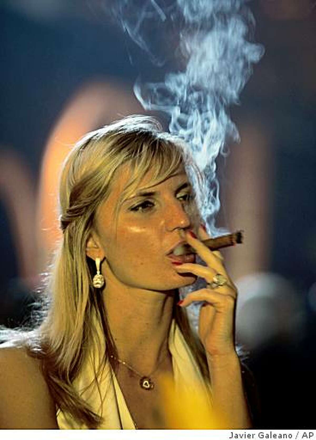 A woman smokes a cigar at a gala dinner closing the 11th annual Cigar Festival in Havana, Friday, Feb. 27, 2009.