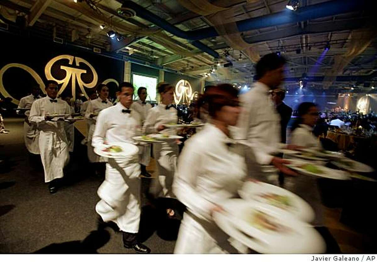 Waiters serve food at a gala dinner closing the 11th annual Cigar Festival in Havana, Friday, Feb. 27, 2009. Cigar enthusiasts from around the world descended on Cuba this week, visiting tobacco farms and factories and savoring new cigar brands during the annual celebration.