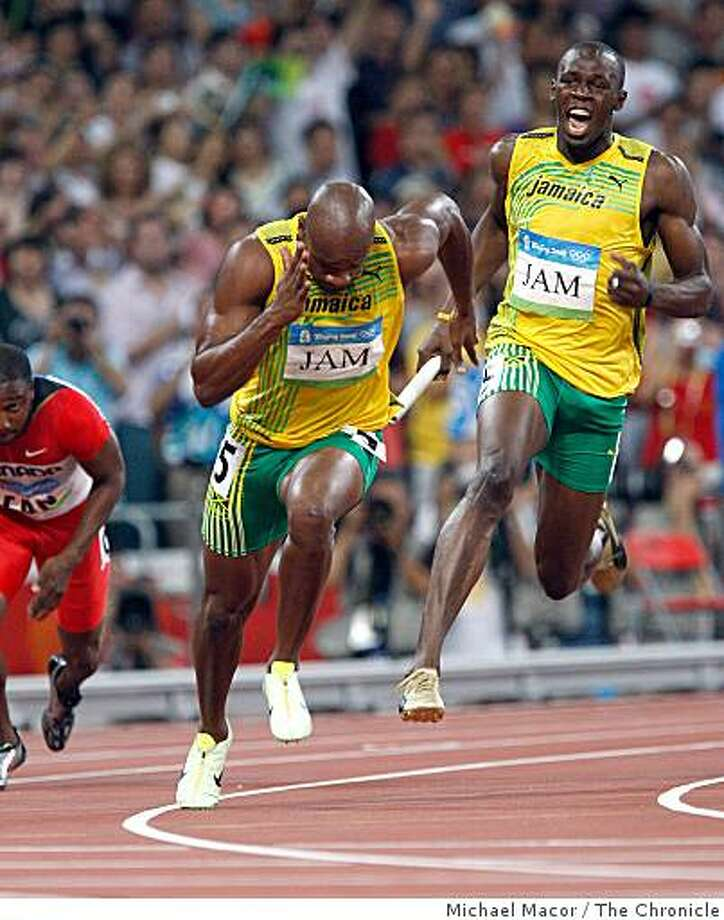 Usain Bolt, rear, prepares to hand off to Asafa Powell on the last leg of the race, as Jamaica's men's 4x100m relay team set a new world record of 37.10 to win the gold medal at the 2008 Olympics in  Beijing, China  on Friday  Aug. 22, 2008. Photo: Michael Macor, The Chronicle