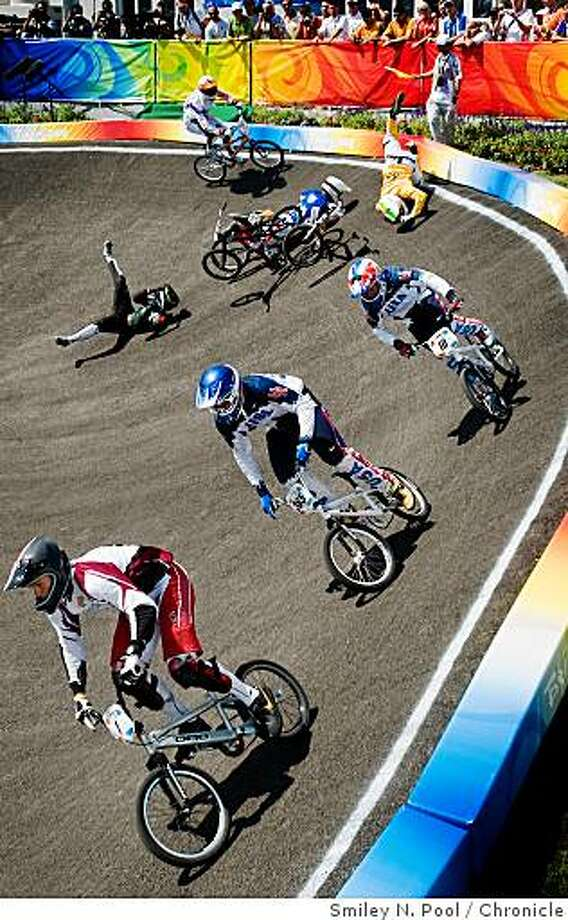 Maris Strombergs of Latvia (1),  Mike Day of the USA (365) and Donny Robinson of the USA (10) head to a 1, 2, 3, finish in the final race of BMX cycling as the riders behind them crash to the track. Photo: Smiley N. Pool, Chronicle