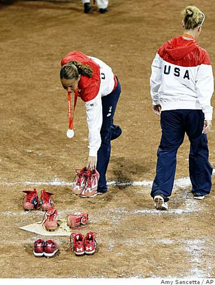 USA's Cat Osterman, left, leaves her spikes on the plate after losing to Japan the softball gold medal. Photo: Amy Sancetta, AP