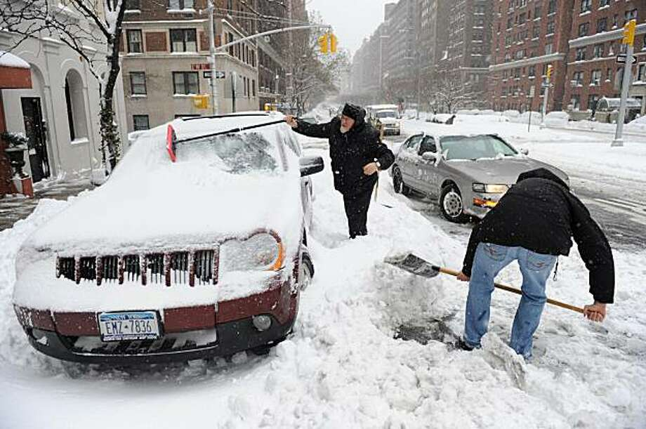 Two men dig out a vehicle on Park Avenue February 26, 2010 after a snow storm dropped 9.4 inches (23.8 cm) in New York. More snow is expected in the next two days. Photo: Stan Honda, AFP/Getty Images