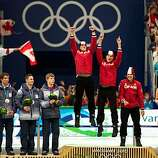 USA speed skaters, from left, Trevor Marsicano, Jonathan Kuck, Chad Hedrick and Brian Hansen watch as the team from Canada celebrates on the awards stand after the USA captured the silver medal in the men's team pursuit speed skating at the 2010 Winter OlUSA speed skaters, from left, Trevor Marsicano, Jonathan Kuck, Chad Hedrick and Brian Hansen watch as the team from Canada celebrates on the awards stand after the USA captured the silver medal in the men's team pursuit speed skating at the 2010 Winter Olympics on Saturday, Feb. 27, 2010, in Vancouver. Canada won the gold.
