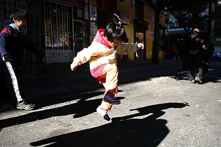 A young girl catches air as she jumps on a Pop pop that didn't pop in San Francisco's Chinatown on the first day of the Lunar New Year. Photo: Lea Suzuki, The Chronicle