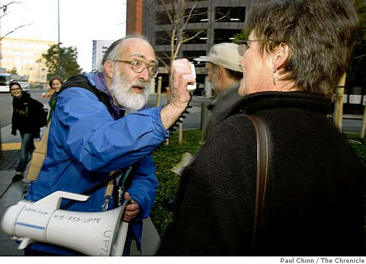 Nino Maida (left), chief steward of the University Professional and Technical Employees union, urges a picketing member to shout into a bullhorn during a rally before the UC Regents meeting at the UCSF Mission Bay campus in San Francisco, Calif., on Wednesday, Feb. 4, 2009.