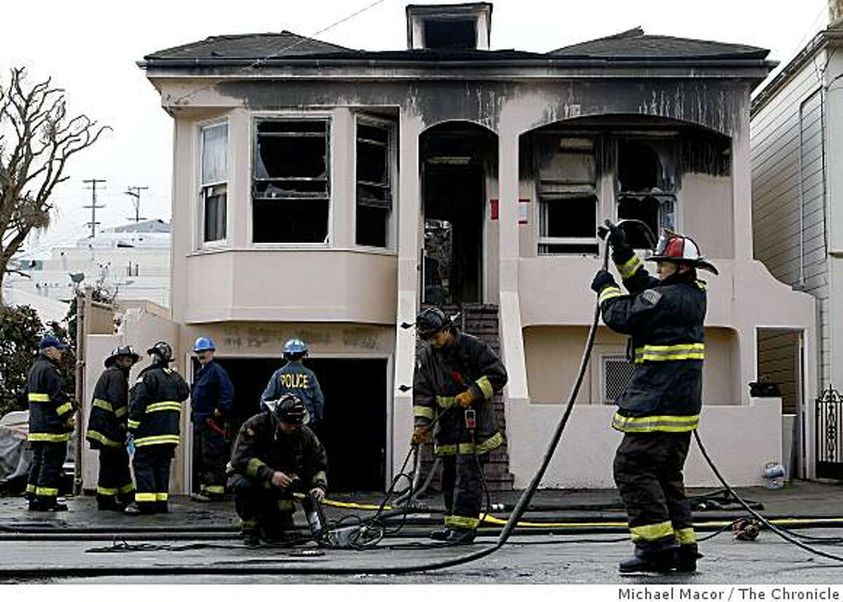 Firefighters clean up the scene of an early morning fire at 627 Felton St. in San Francisco. The fire left one firefighter with life-threatening injures.