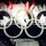 A snow boarder jumps through giant Olympic rings to kick-off the opening ceremony for the Winter Olympic Games at BC Place stadium in Vancouver, B.C., on Friday.