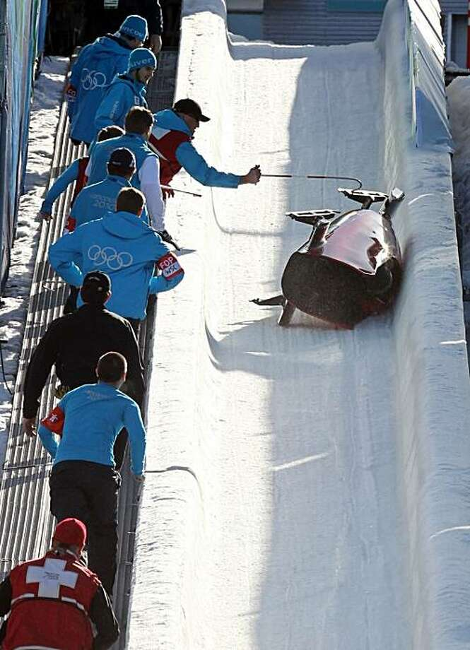 Medical personnel race in to help as Italy's ITA-2, piloted by Fabrizio Tosini overturns during a training run for the men's two-man bobsled at the Vancouver 2010 Olympics in Whistler, British Columbia, Friday, Feb. 19, 2010. Photo: Michael Sohn, AP