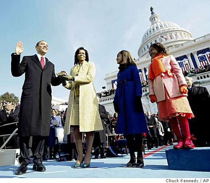 Barack Obama, left, takes the oath of office from Chief Justice John Roberts, not seen, as his wife