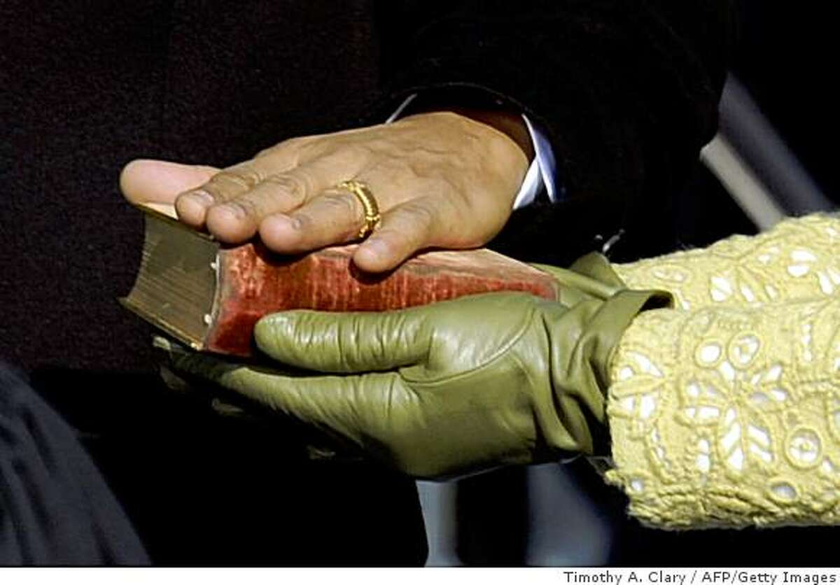 Barack Obama's hand lies on a bible as he is sworn in as the 44th US president by Supreme Court Chief Justice John Roberts in front of the Capitol in Washington on January 20, 2009.