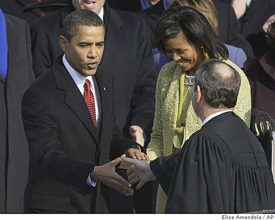 President Barack Obama, left, shakes hands with Chief Justice John Roberts after taking the oath of office. Photo: Elise Amendola, AP