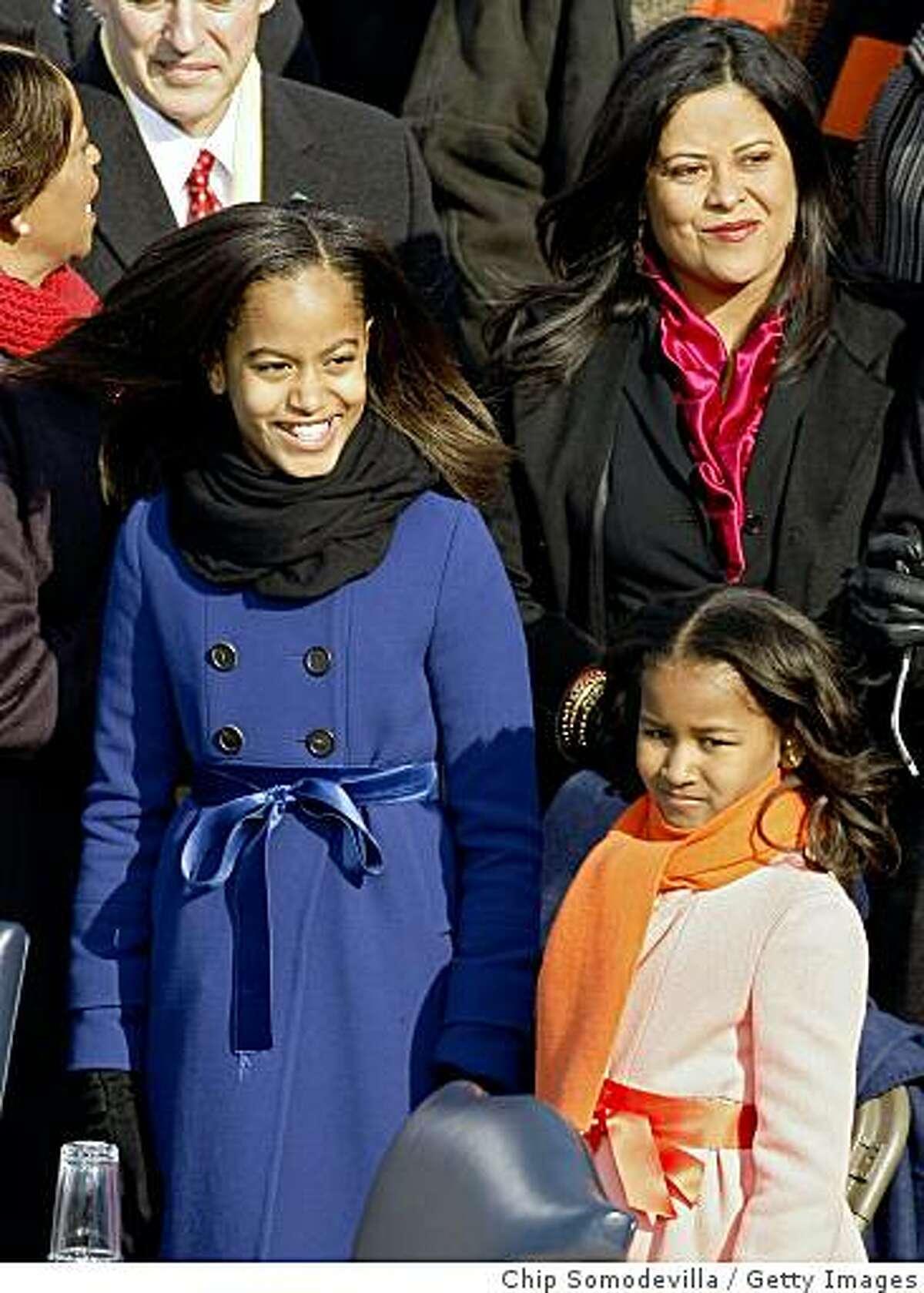 Malia and Sasha Obamam stand on the stage ahead of the inauguration.