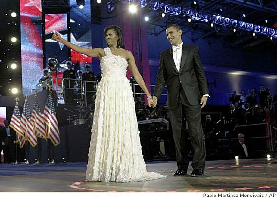 President Barack Obama, right, and first lady Michelle Obama, left, appear at the Neighborhood Inaugural Ball in Washington, Tuesday, Jan. 20, 2009. Photo: Pablo Martinez Monsivais, AP