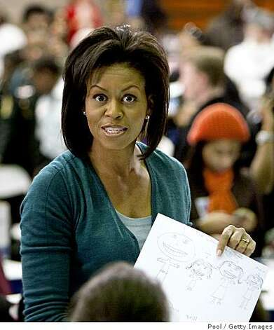 "WASHINGTON - JANUARY 19:  Michelle Obama holds a picture a young girl drew of her family at Calvin Coolidge High School where students, military families, and volunteer service groups are working on various projects supporting the troops on January 19, 2009 in Washington, DC. Obama stopped at Calvin Coolidge High School to promote his ""Day of Service"" program. (Photo by Joshua Roberts-Pool/Getty Images) Photo: Pool, Getty Images"