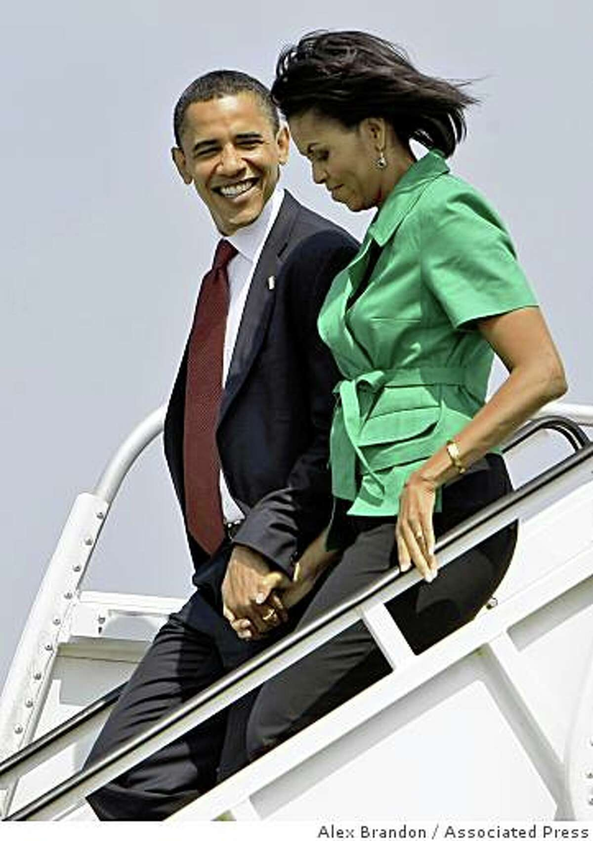 Democratic presidential candidate Sen. Barack Obama D-Ill., and his wife Michelle, walks down the steps of his campaign charter plane, Friday, June 13,2008, in Columbus, Ohio. (AP Photo/Alex Brandon)
