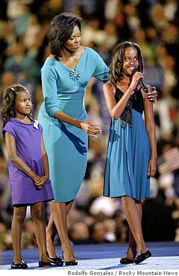 Michelle Obama and her children Sasha, left and Malia say hi to Democratic Presidential hopeful  Sen. Barack Obama, who was being broadcast live into the Democratic National Convention at the Pepsi Center in Denver on Aug. 25, 2008. Photo: Rodolfo Gonzalez, Rocky Mountain News