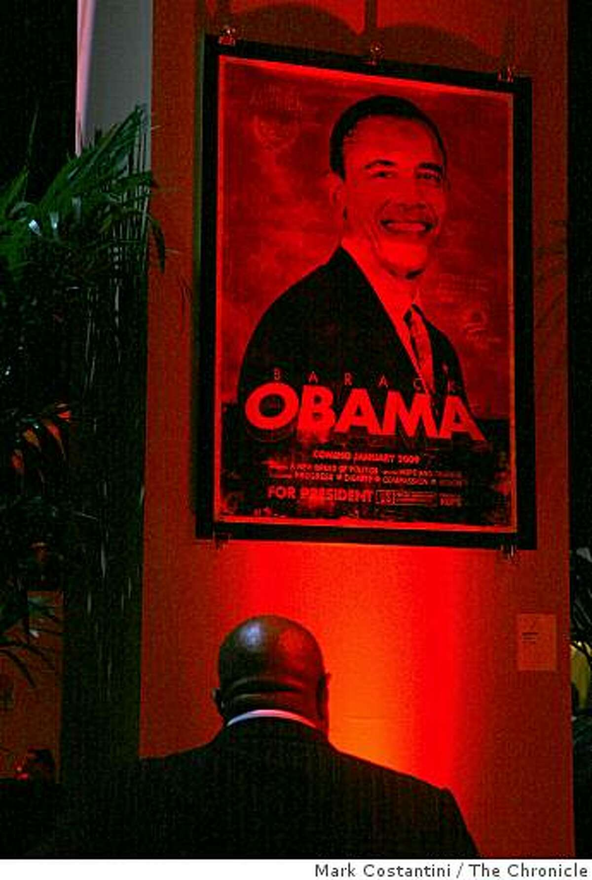 A partygoer looks at an Obama poster at the Inauguration West party celebrating the inauguration of Barack Obama at the Metreon in San Francisco, Calif. on Tuesday January 20, 2009.
