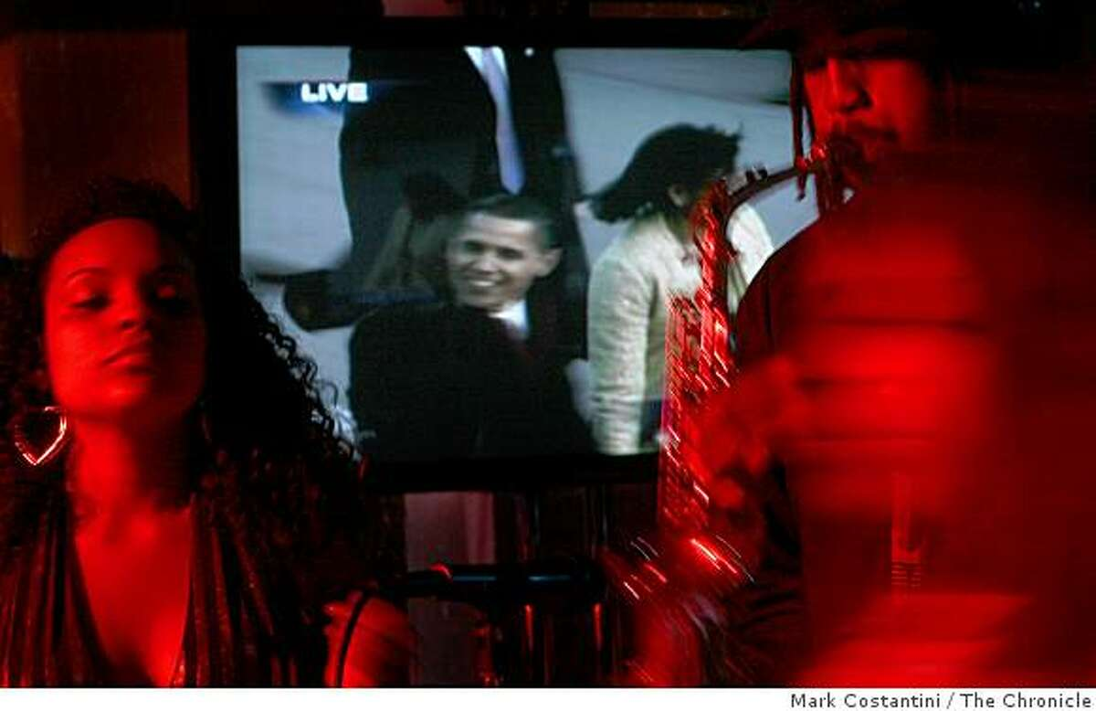A television shows the inauguration as the band the Kev Choice Ensemble plays at the Inauguration West party celebrating the inauguration of Barack Obama at the Metreon in San Francisco, Calif. on Tuesday January 20, 2009.
