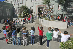 """Kindergarteners from Malcolm X Elementary School in Berkeley lined up to attach their wishes to a """"Peace Tree"""" for President Obama."""