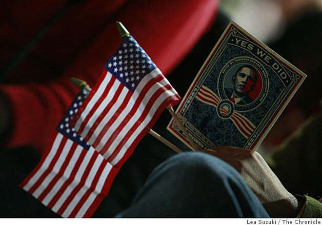 American flags and a sticker with President Barack Obama's image are held in hand in Oakland, Calif. on Tuesday January 20, 2009. Photo: Lea Suzuki, The Chronicle