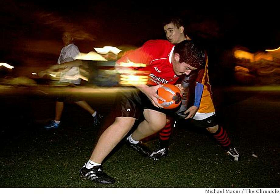 Jamie Rodriguez, (with ball) runs into blocker Felipe Lopez, players of the Warhogs rugby team runnng drills as they practice in near darkness at the Carmen Flores Recreation Center in Oakland, Calif, .on Wednesday Jan. 14, 2009. Photo: Michael Macor, The Chronicle