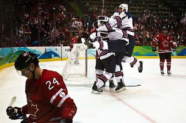 USA players mob Ryan Kesler after his empty net goal in the final minute gave the USA a 5-3 victory over Canada's Corey Perry (24) and his teammates in men's hockey preliminary round action at the 2010 Winter Olympics on Sunday, Feb. 21, 2010, in VancouvUSA players mob Ryan Kesler after his empty net goal in the final minute gave the USA a 5-3 victory over Canada's Corey Perry (24) and his teammates in men's hockey preliminary round action at the 2010 Winter Olympics on Sunday, Feb. 21, 2010, in Vancouver. Photo: Smiley N. Pool, Chronicle Olympic Bureau