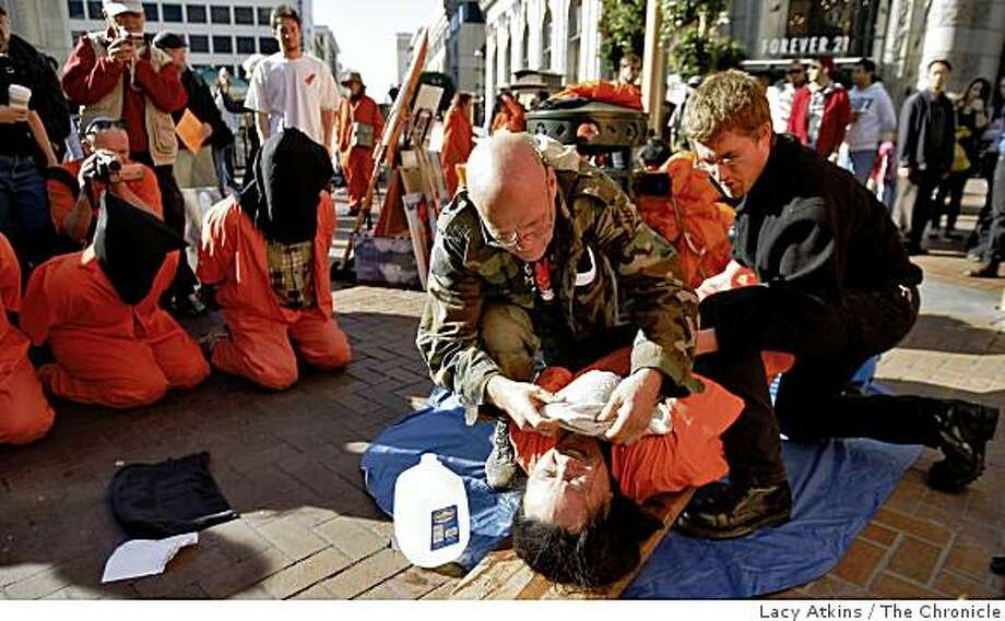 Michael Dean( left) holds Noel Juan down and simulates water boarding at a protest marking the 7th anniversary onf the U.S. interrogation of prisoners in Guantanamo Bay, Sunday Jan. 11, 2009, in San Francisco, Calif. Photo: Lacy Atkins, The Chronicle