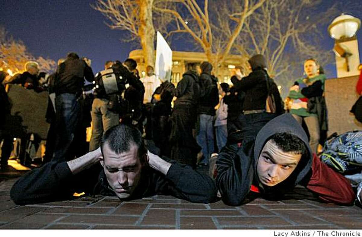 Timothy Andrews (left) and Alexander Roe lay in protest over the killing of Oscar Grant, rally at BART's Civic Center, Monday Jan. 12, 2009, in San Francisco, Calif.