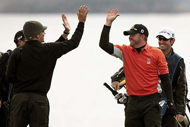J.B. Holmes right, is congratulated by Garrett Willis after making a Eagle on his second shot on the 8th hole at Pebble Beach Thursday February 11, 2010. Holmes finished with a score of 65, seven shots under par to lead the AT&T Pro-Am on the first day of the four day tournament in Pebble Beach Ca. Photo: Lance Iversen, The Chronicle