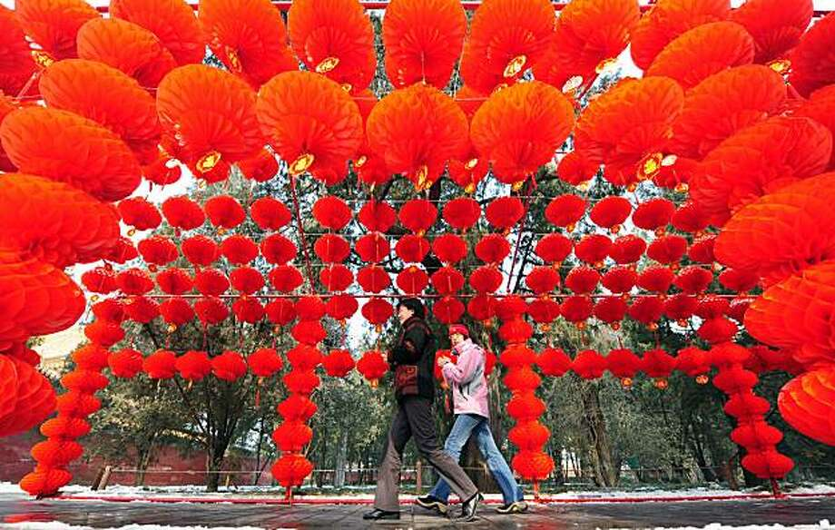 People walk beneath a display of red lanterns at the Temple of the Earth (Ditan) Park in Beijing on February 8, 2010, displayed for the coming Lunar New Year celebrations, China's most important holiday season also known as Spring Festival, which begins on February 14. The centuries old tradition of hanging red lanterns remains ever popular across China, where they are widely used for festivals and holidays, at weddings and other personal celebrations, with the colour considered auspicious, signifying reunion, health, happiness, harmony, peace and prosperity. TOPSHOTS Photo: Frederic J. Brown, AFP/Getty Images