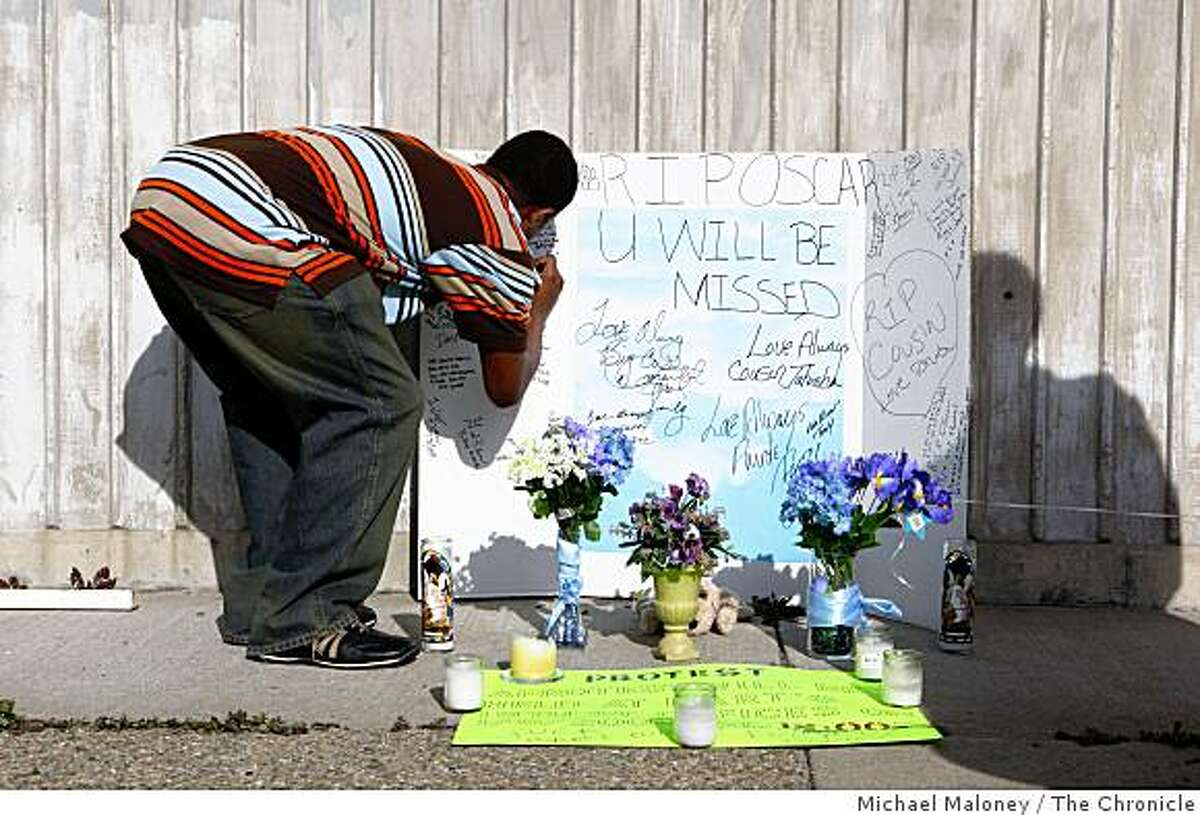 Jimmie Brown, first cousin to Oscar Grant signs a poster at a makeshift memorial at the Fruitvale BART station on January 4, 2009, near where Oscar Grant was shot by a BART officer on New Years Day.