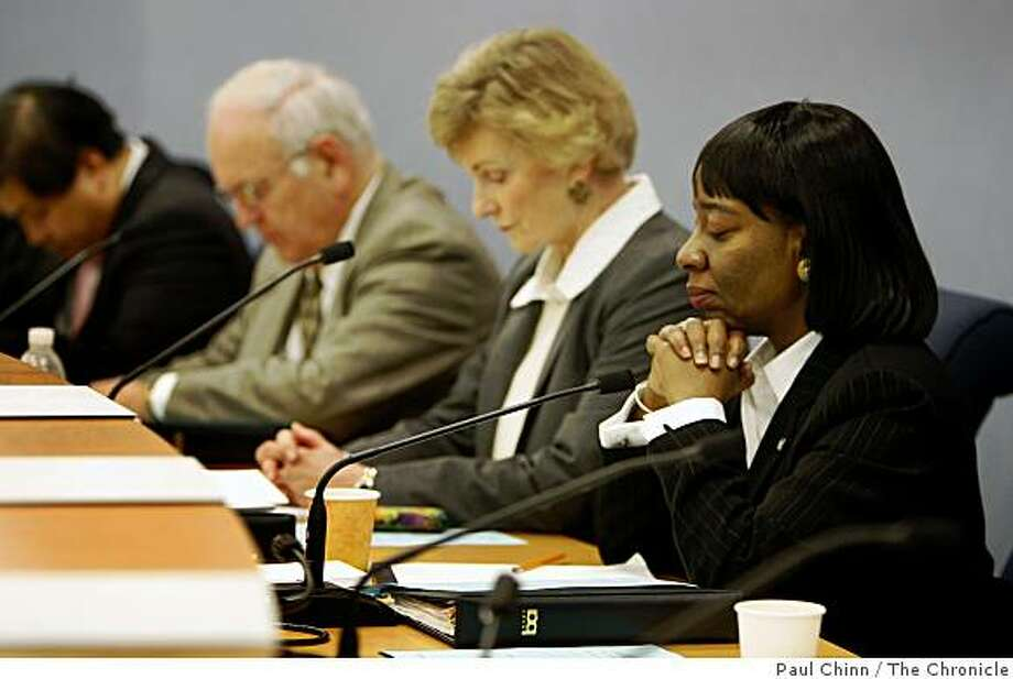 BART director Lynette Sweet bows her head in a moment of silence to honor Oscar Grant before the BART board of directors meeting on Thursday. Joining her are fellow directors (from left) James Fang, Thomas Blalock and Gail Murray. Grant was shot to death by a BART police officer in the early hours of New Years Day. Photo: Paul Chinn, The Chronicle