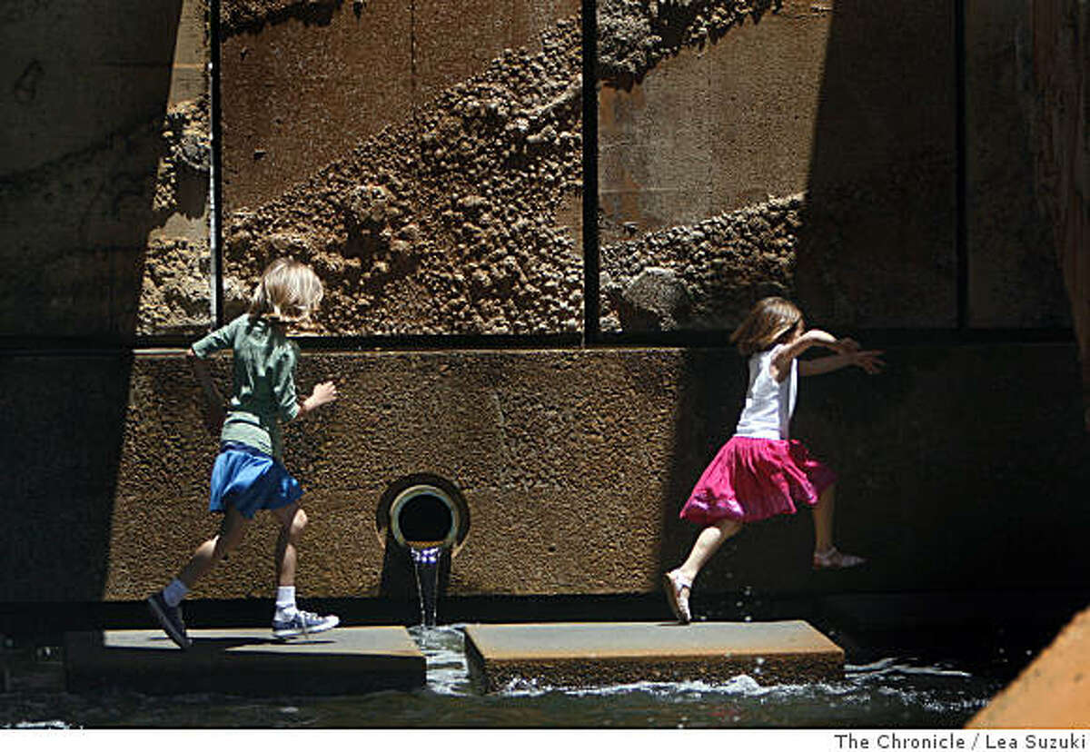 Kelly O'Donnell, 9 (l to r) and Kristen O'Donnell, 6, race under the fountain at Justin Herman Plaza while enjoying an outing in San Francisco, Calif. with their grandparents on their last day of school on Wednesday June 11, 2008. Photo By Lea Suzuki/ The Chronicle