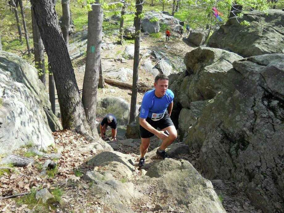Ridgefield resident Michael Byl participates in a race called the North Face Challenge 50k trail run in May 2011 in Bear Mountain, N.Y.  He is climbing a 20-foot rock ledge. Photo: Contributed Photo