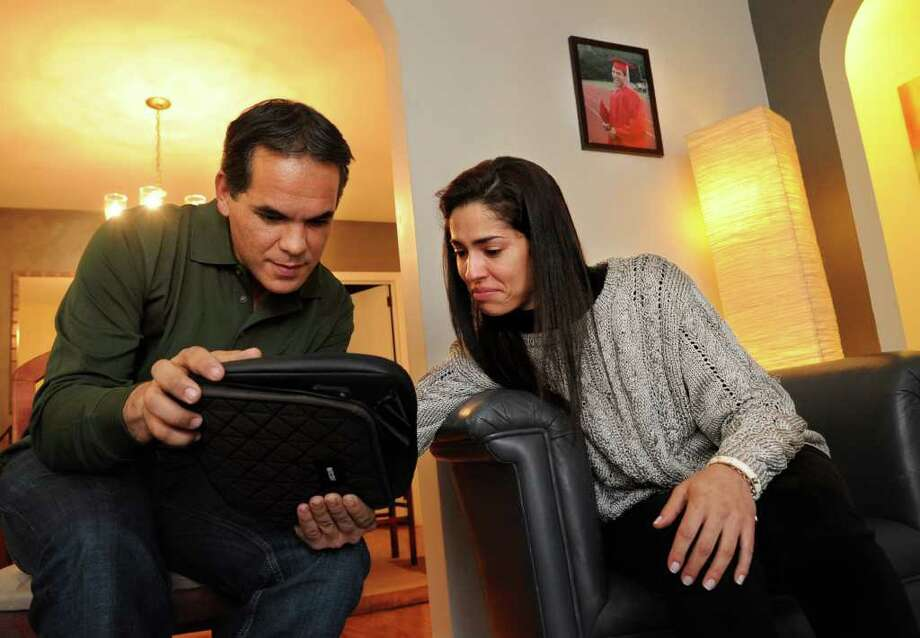 A photo of Lucas Silva at his high school graduation hangs on the wall as his cousin, Thatiane Faria, right, and family friend Celio Silva look at photos of Lucas on an iPad on Friday, December 30, 2011. Lucas Silva and his friend, Felipe Chagas were killed while changing a tire off the shoulder of Interstate-95 in October 2010. Photo: Lindsay Niegelberg / Stamford Advocate