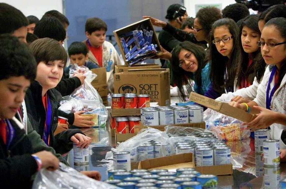 Stevenson Middle School students bag donated goods during the kickoff of Souper Bowl of Caring Houston 2012 at the Houston Food Bank Wednesday, Jan. 11, 2012, in Houston. Photo: Cody Duty, Houston Chronicle / © 2011 Houston Chronicle