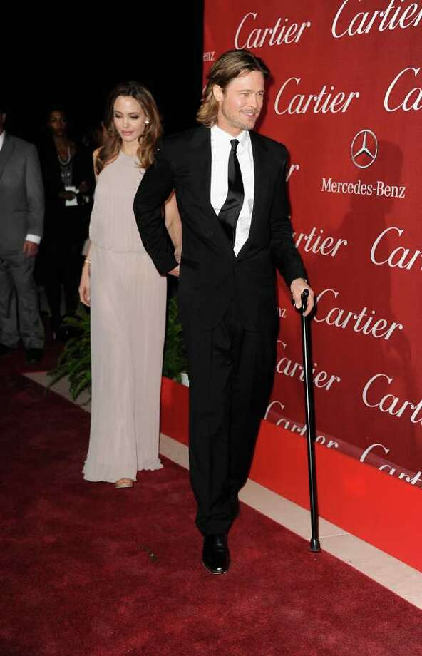 "Brad Pitt, 49, hobbles down the red carpet with wife Angelina Jolie and a cane at the 2012 Palm Springs International Film Festival Awards Gala on Jan. 7 in Palm Springs, California. He told reporters that he slipped on a hill while carrying daughter Vivienne and injured a knee ligament. ""It was either her or me,"" he said. Photo: Frazer Harrison, Getty Images / 2012 Getty Images"