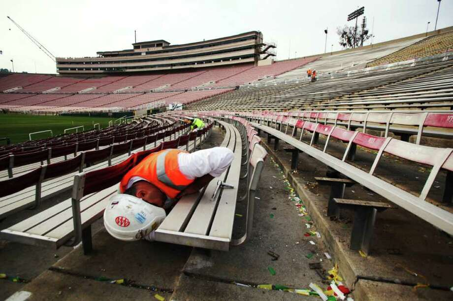 Construction worker John Baron unbolts seats in preparation for tunnel widening and new aisles as phase two of the renovation of the Rose Bowl stadium continues with the demolition of the press box and other construction Wednesday, Jan. 11, 2012.  When completed, the press box will increase from about 45,000 square feet to 150,000 square feet.  Other projects in phase two include widening of tunnels, adding new aisles, concrete and wall repair on the north side of the stadium. The three-year project is expected to be completed in time for the 100th Rose Bowl football game in 2014. (AP Photo/Reed Saxon) Photo: Reed Saxon, Associated Press / AP