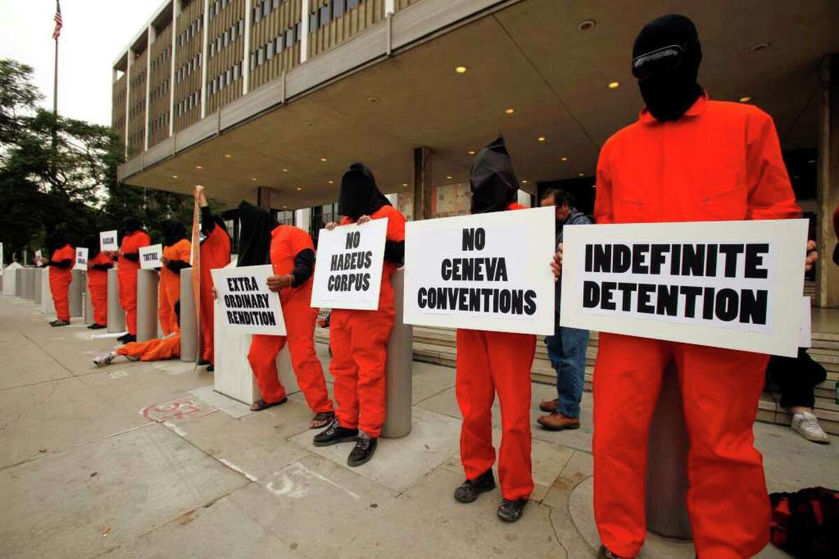 """Human rights activists wearing orange jumpsuits and black hoods, mark the 10th anniversary of the U.S. naval base at Guantanamo Bay, Cuba being used as a detention facility in the """"war on terror,'' outside the Los Angeles Federal Building in Los Angeles Wednesday, Jan. 11, 2012. (AP Photo/Damian Dovarganes)"""