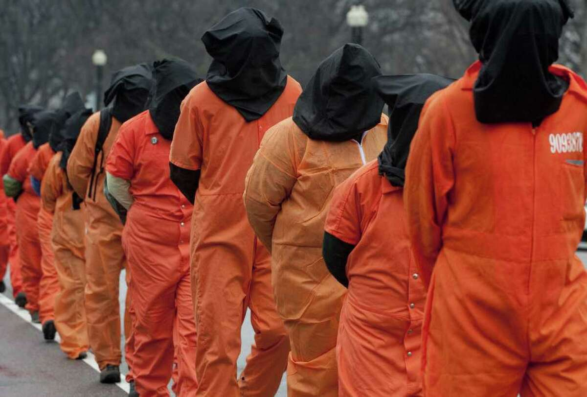 Protesters wearing orange prison jump suits and black hoods march during a protest against holding detainees at the military prison in Guantanamo Bay during a demonstration on Capitol Hill in Washington, DC, on January 11, 2012, the 10th anniversary of the arrival of the first group of detainees to be held at the prison. Protesters marched down Pennsylvania Avenue from the White House, past the US Capitol before finishing at the US Supreme Court. AFP PHOTO / Saul LOEB
