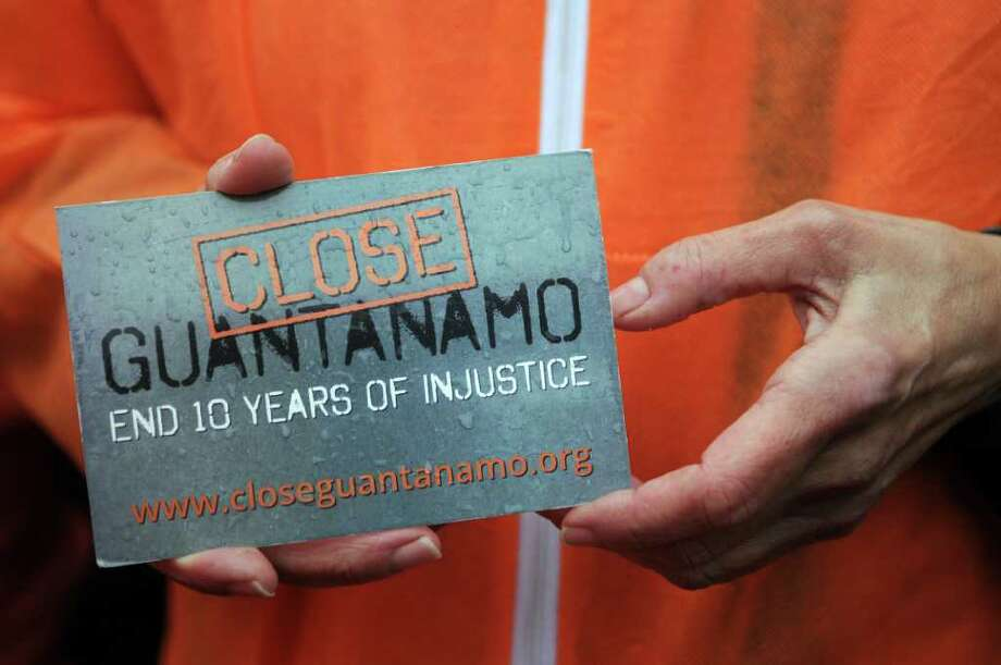 WASHINGTON, DC - JANUARY 11: A member of the organization Witness Against Torture wears an orange prison jump suit and holds a card in her hand during a demonstration urging the government to close down the detention facility at Guantanamo Bay, in Lafayette Park outside the White House January 11, 2012 in Washington, DC. Protesters carry on a 92-hour vigil in a protest of the 10th anniversary of the arrival of the first group of detainees to arrive at the US military facility Photo: Astrid Riecken, Getty Images / 2012 Getty Images