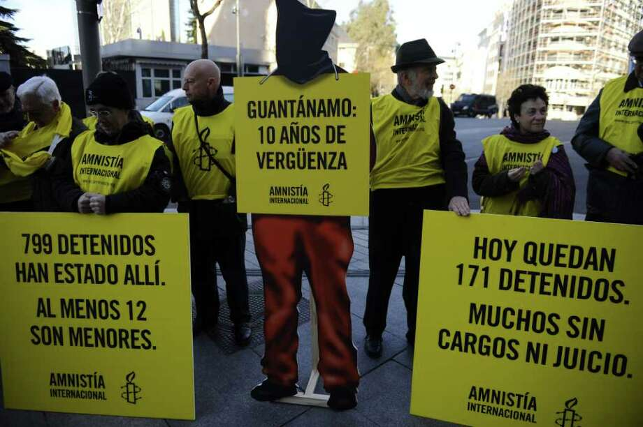 "Amnesty International activists, dressed in orange jumpsuits similar to those worn by prisoners at the US detention camp in Guantanamo Bay, demonstrate on January 11, 2012 in front of the US embassy in Madrid against the 10th anniversary of the opening of the prison, which President Barack Obama vowed to shut down in one of his first acts in office. The Guantanamo Bay prison was opened at a US naval base in Cuba on January 11, 2002 to house ""war on terror"" prisoners captured as the United States ramped up military efforts in Afghanistan and elsewhere around the world in response to the US attacks, and to combat global terrorism. Banners read "" Guantanamo : 10 years of shame"" ""There are still 171 prisoners, at least 12 minors.""  AFP PHOTO / PIERRE-PHILIPPE MARCOU Photo: PIERRE-PHILIPPE MARCOU, AFP/Getty Images / AFP"