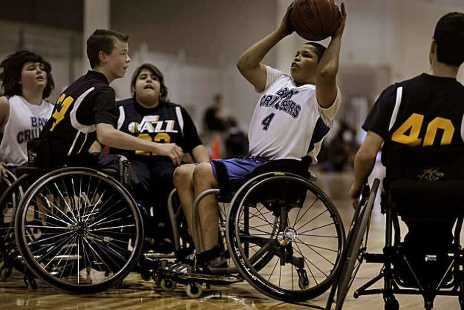 Guarded by Spencer Helsop, (24), Aimee Vargas, (22) and Jason Hall, (40), Chris Rodriguez, (4)  takes a shot as the Bay Cruisers take on the Utah Jazz in wheelchair basketball on Saturday Feb. 5, 2011 in Hayward, Ca. Chris Rodriguez, who is currently paralyzed from the waist down after being hit by a stray bullet while attending a piano lesson in January of 2008, has taken up wheelchair basketball. Photo: Michael Macor, The Chronicle