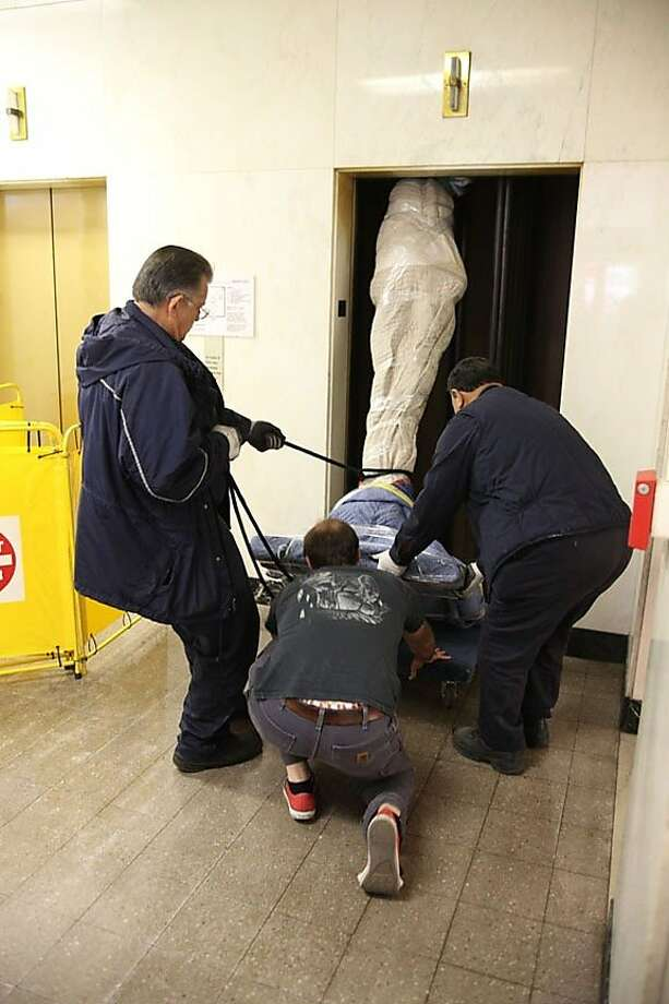 "an elevator crew unloads Stephen De Staebler's bronze sculpture ""Winged Figure Ascending"" (2011) from beneath the cabin of the passenger elevator used to lift the 410-lb. object to the second floor Dolby Chadwick Gallery for De Staebler's first posthumous exhibition Photo: Unknown"