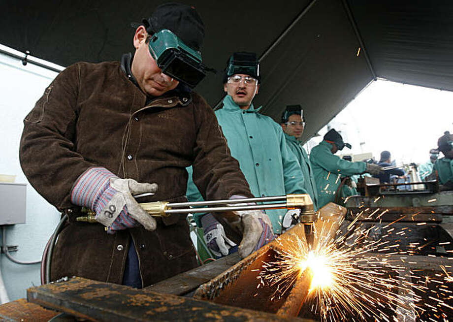 Michael Means practices cutting a steel beam using an acetylene torch with classmate Victor Moran (center) in a welding class at CCSF's Evans Campus in San Francisco, Calif., on Tuesday, March 8, 2011. Photo: Paul Chinn, The Chronicle