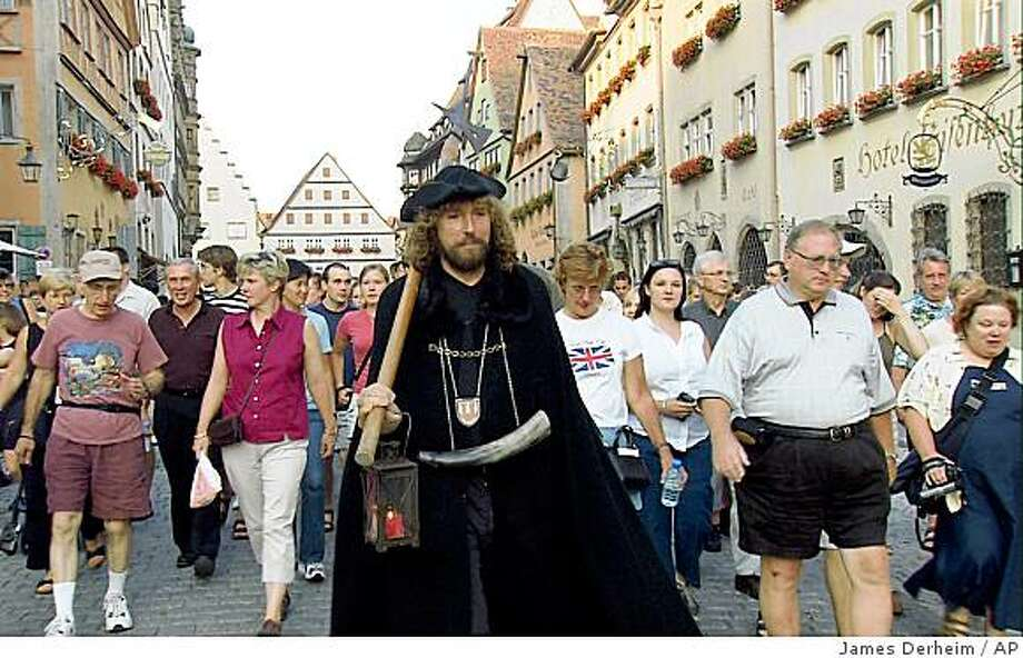 This undated photo provided by Rick Steves' Europe Through the Back Door, shows tour guide Hans-Georg Baumgartner in his role as the Night Watchman in Rothenburg, Germany. Baumgartner gives tourists a taste of what life was like centuries ago in the medieval walled town, while carrying a hellebarde, a long, hooked spear that watchman used for protection while making their nightly rounds. Photo: James Derheim, AP