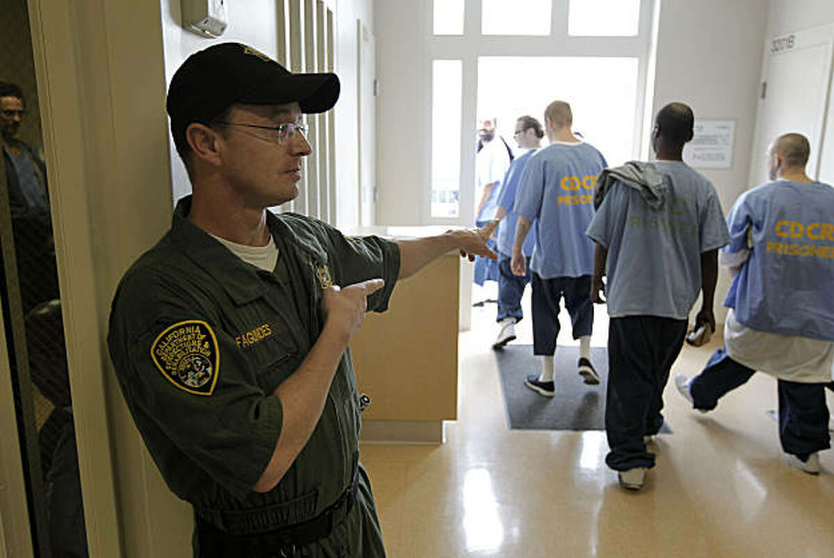 Corrections office, Daniel Fagundes, directs prisoners, inside San Quentin State Prison, on Friday Mar. 4, 2011, in San Quentin, Ca. California State prison guards and their supervisors, have racked up an astounding 33 million hours of vacation, sick and other paid time off, which could amount to as much as a $1 billion liability for the state. A Senate report warned, a year ago, that mandatory furloughs at a 24-7 agency, would lead to such future burdens.